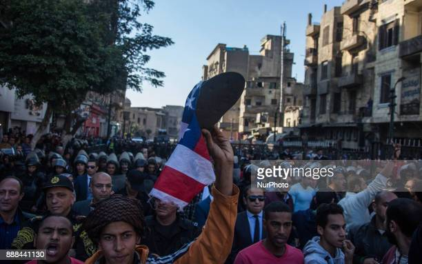 A man an American flag and a shoe during a protest after a recent US decision to recognize Jerusalem as the capital of Israel in Cairo Egypt Friday...