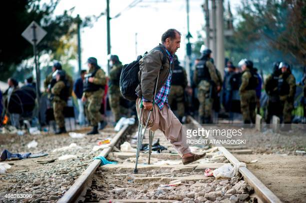 A man an amputee walking on crutches walks over railway tracks past a group of Macedonian police officers facing migrants demonstrating as they wait...