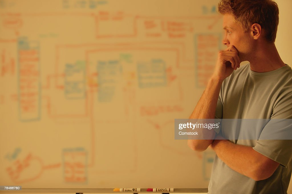 Man analyzes workflow chart : Stock Photo