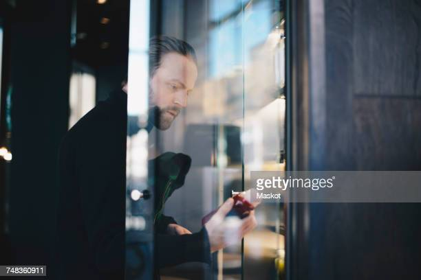 Man analyzing bottle while looking at display cabinet in store
