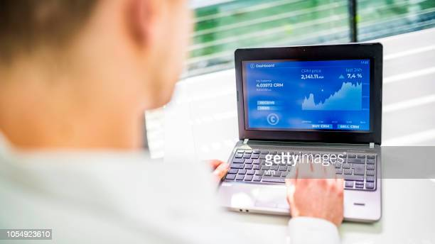 man analyzing cryptocurrency graphs on his laptop - financial technology stock photos and pictures