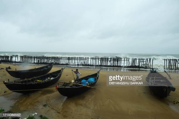 A man anchors boats at the Tajpur Beach ahead of the expected landfall of cyclone Amphan in Midnapore West Bengal on May 20 2020 Several million...