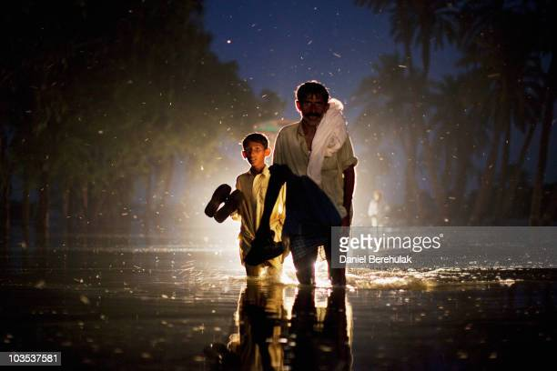 A man and a boy displaced by floods walk through flood waters on August 22 2010 in the village of Baseera near Muzaffargarh in Punjab Pakistan The...