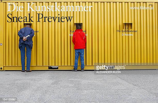 A man and a boy look at an art exhibition preview of the Kunstkammer Wien displayed in a freight container in front of the Kunsthistorisches Museum...
