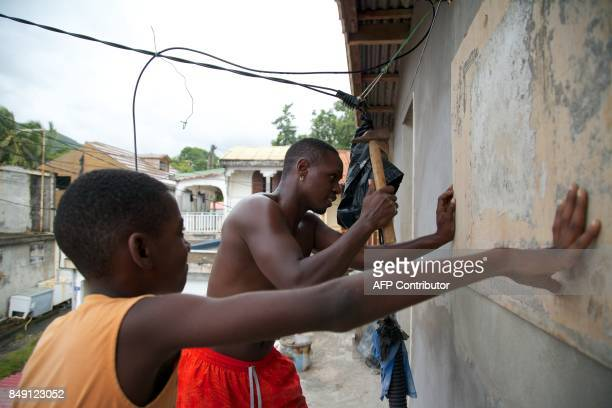 TOPSHOT A man and a boy nail a board over a window on September 18 in TroisRivieres on the Fench Caribbean island of Guadeloupe as Hurricane Maria...