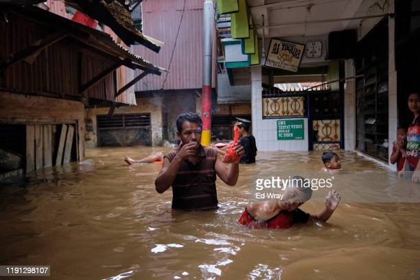 A man and a boy navigate through their flooded neighborhood on January 2 2020 in Jakarta Indonesia Flooding caused by heavy rain left at least 17...