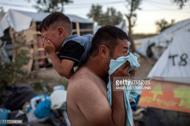 TOPSHOT A man and a boy react cry after police fired tear gas during clashes outside the refugee camp of Moria on the Greek island of Lesbos on...