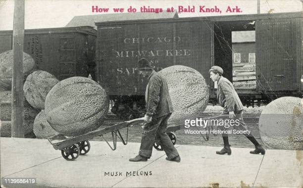 A man and a boy use dollies to haul giant musk melons near a train Waupun Wisconsin 1911 In red text on the upper center portion is the inscription...