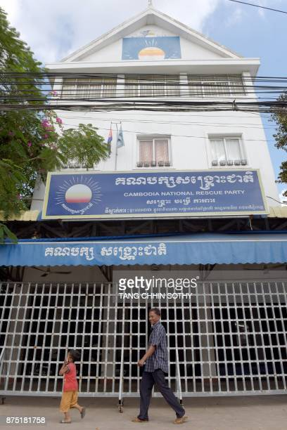 Man and a boy walk past the opposition Cambodia National Rescue Party headquarters in Phnom Penh on November 17 a day after the party was outlawed by...