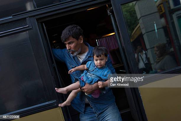 A man and a child disembark a bus from Proshevo at the main bus station on September 6 2015 in Belgrade Serbia Many migrants short on financial...