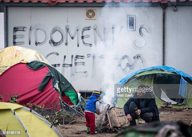 A man and a child gather besides a fire at the Idomeni refugee camp on the Greek Macedonia border on March 17 2016 in Idomeni Greece Many of the...