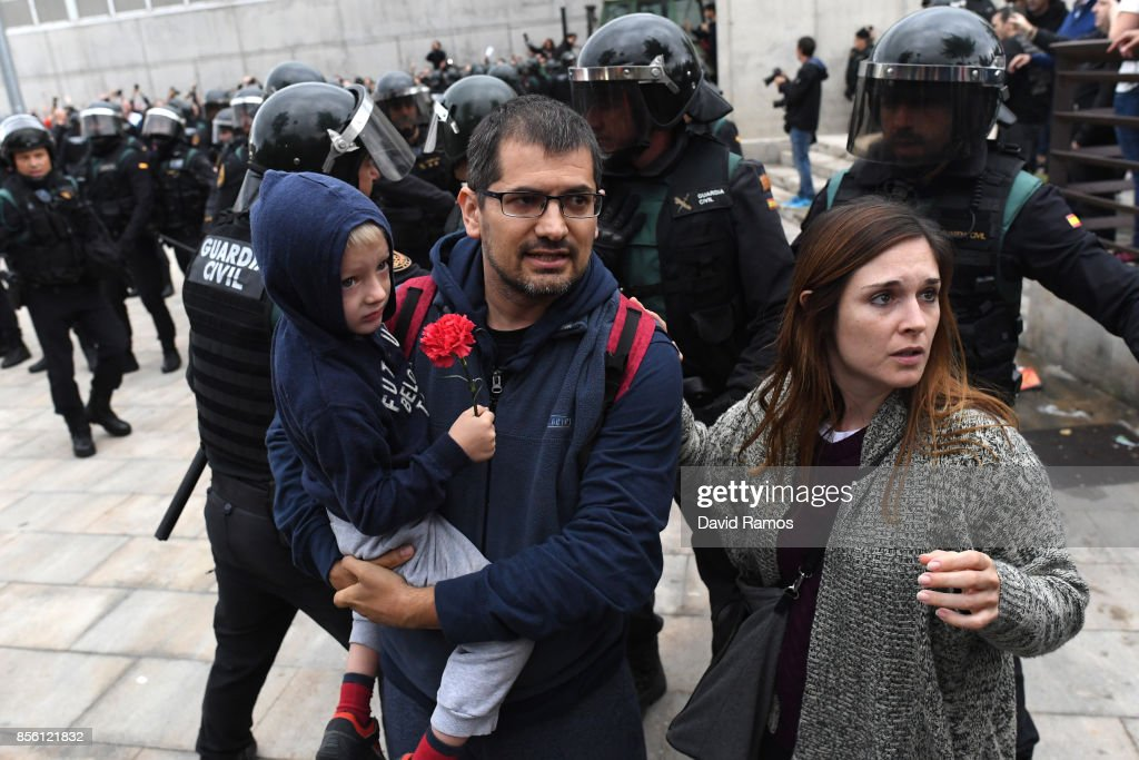 A man and a child holding a red flower run from the police as they move in on the crowds as members of the public gather outside to prevent them from stopping the opening and intended voting in the referendum at a polling station where the Catalonia President Carles Puigdemont will vote later today on October 1, 2017 in Sant Julia de Ramis, Spain. More than five million eligible Catalan voters are estimated to visit 2,315 polling stations today for Catalonia's referendum on independence from Spain. The Spanish government in Madrid has declared the vote illegal and undemocratic.