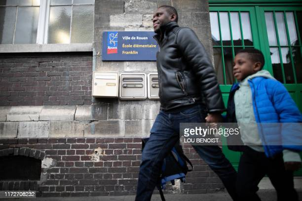 A man and a child leave the Franklin elementary school after parents were asked to pick up their children from the school in Rouen northern France on...