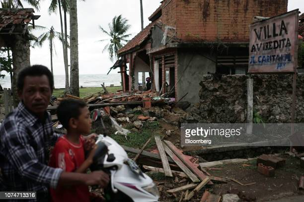A man and a child ride on a motorcycle past a damaged building at the Villa Avi Redita in Carita Banten province Indonesia on Monday Dec 24 2018...