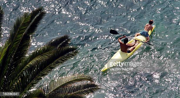 A man and a child row a canoe during the summer holidays on August 22 2012 in Nice southeastern France AFP PHOTO / VALERY HACHE