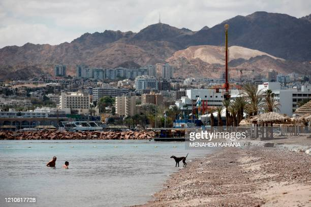 Man and a child swim at an empty Red Sea beach in the southern Israeli resort city of Eilat on April 17, 2020 amid the coronavirus COVID-19 pandemic....