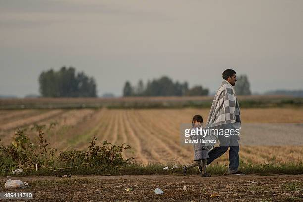 Man and a child walk the last few kilomtres from Serbia to Croatia as more migrants continue to arrive by bus on September 21, 2015 in Sid, Serbia....