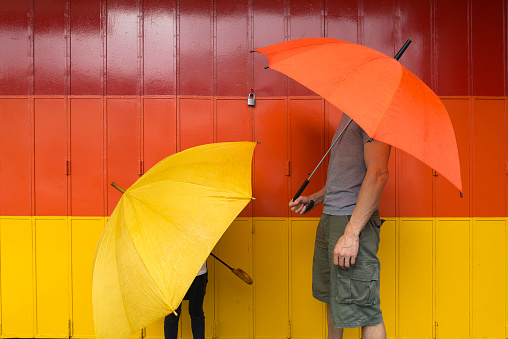 A man and a child with a yellow and orange umbrellas, the matching colours for the painted gate behind. - gettyimageskorea
