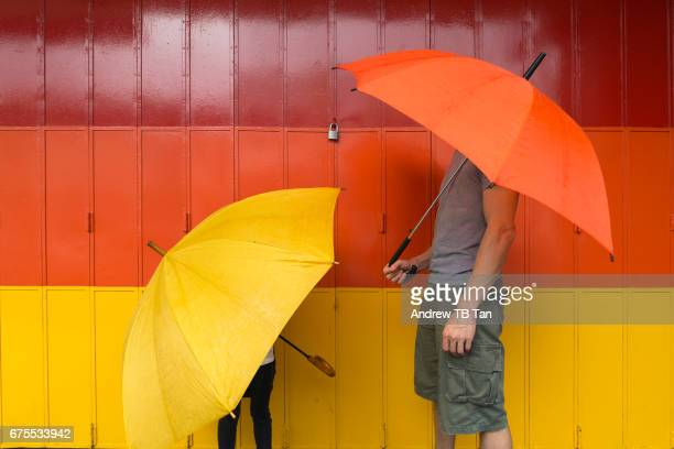 a man and a child with a yellow and orange umbrellas, the matching colours for the painted gate behind. - mimica fotografías e imágenes de stock