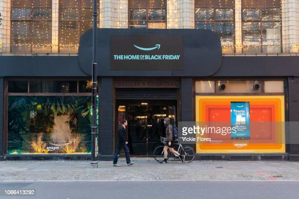 A man and a cyclist walk past the Amazon Black Friday popup shop in Shoreditch east Lonon on November 23 2018