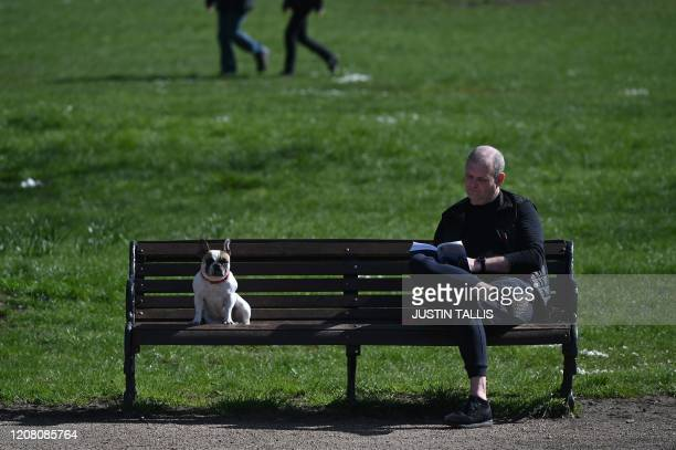 A man and a dog sit on a park bench on Clapham Common in south London on March 24 2020 after Britain's government ordered a lockdown to slow the...