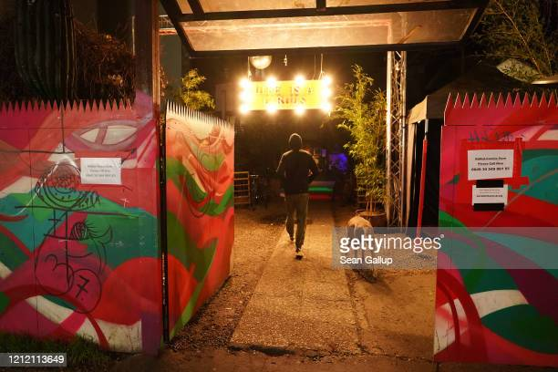 Man and a dog walk into the famed KitKat Club as signs outside refer to the coronavirus on March 12, 2020 in Berlin, Germany. City authorities are...
