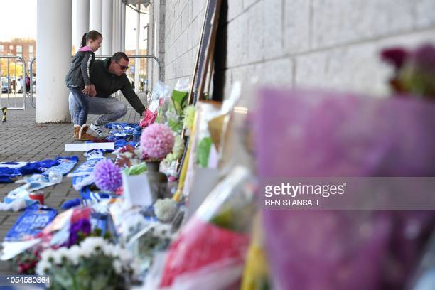 A man and a girl add to flowers and Leicester City scarfs left as tributes outside Leicester City Football Club's King Power Stadium in Leicester...