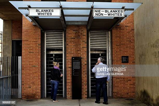 A man and a girl enter through the reproduction of a segregated gate on May 19 2010 at the Apartheid museum in Johannesburg South Africa The...