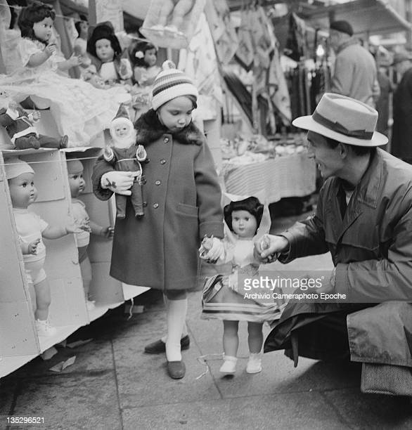 A man and a girl playing with a doll at a market stall in Rome circa 1960
