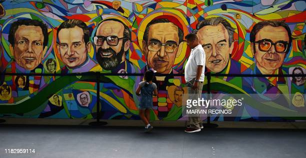Man and a girl stand in front of a mural in homage of six Jesuit priests and two employees murdered during the civil war on the 30th anniversary of...