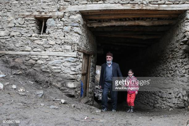 A man and a kid walk around between stone houses at a village at Hizan district in the southeastern province of Bitlis Turkey on February 18 2018...