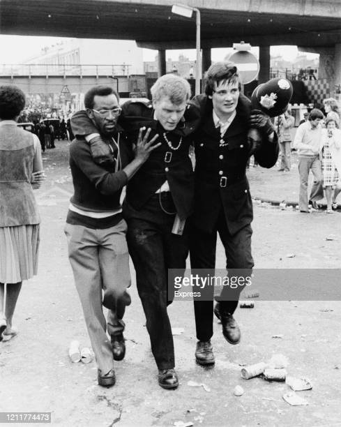 Man and a police officer help an injured police officer during riots at the Notting Hill Carnival, London, UK, 31st August 1976.