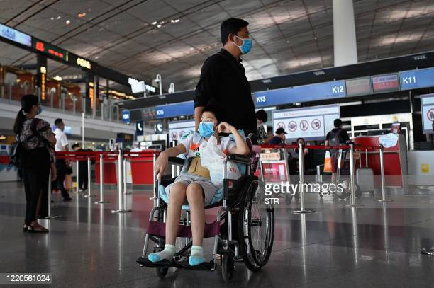 Man and a wheelchair-bound child, both wearing face masks, look on at the Beijing International Airport on June 17, 2020. - Beijing's airports...