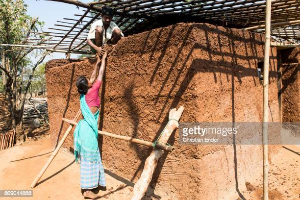 A man and a woman are building together a house made from loam in a rural area about 300 Kilometer from Kolkata