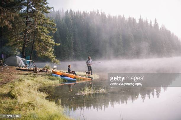 man and a woman are fishing at the mountains - camping stock pictures, royalty-free photos & images