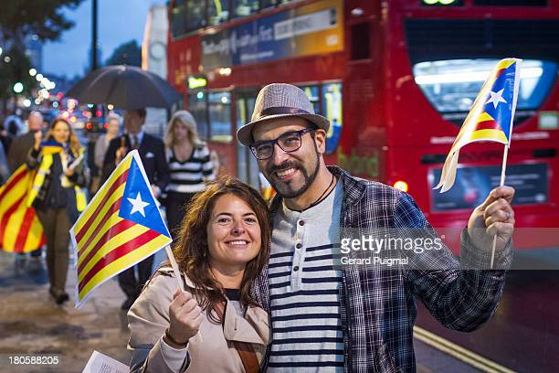 CONTENT] A man and a woman are smiling to the camera while holding proindependence flags of Catalonia in London During the National Day of Catalonia...