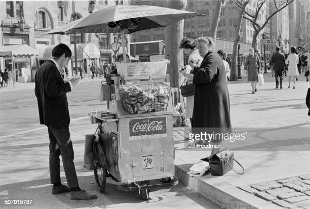 A man and a woman buy food from a street vendor in New York City USA 1966