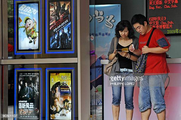 A man and a woman check their movie tickets at a cinema counter in Shanghai on August 17 2009 China said on August 17 2009 it was 'actively' getting...