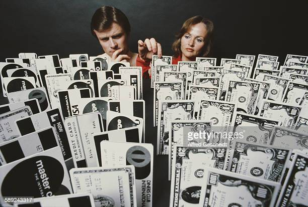 A man and a woman choose from an array of credit cards and dollar banknotes 1979
