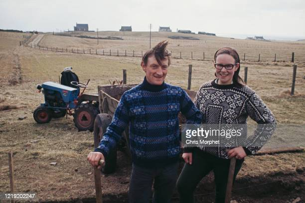 A man and a woman cutting peat on Fair Isle Shetland Islands Scotland June 1970 They are wearing traditional Fair Isle pattern sweaters