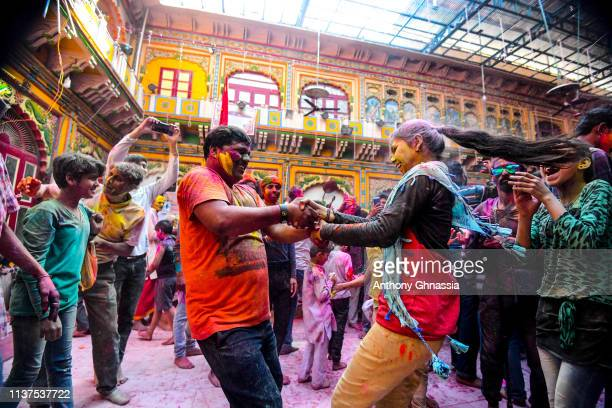 A man and a woman dance during the celebration of the Holi Festival on March 21 2019 At Dwarkadhish Temple in Mathura India