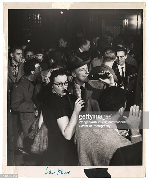 A man and a woman drink bottles of beer at the crowded San Remo bar Greenwich Village New York New York mid 1950s Photo by Weegee/International...