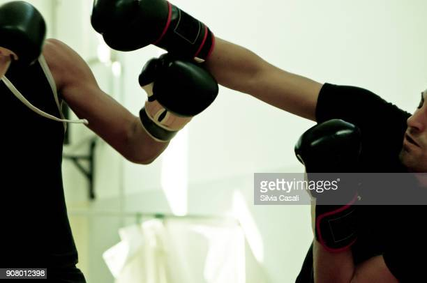 A man and a woman during a kickboxing combat training