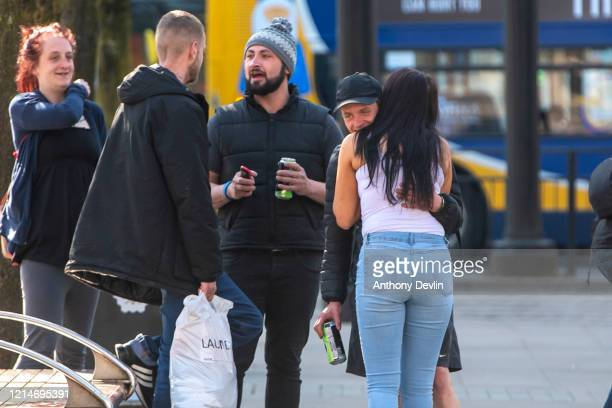 A man and a woman embrace in Piccadilly Gardens on March 25 2020 in Manchester United Kingdom British Prime Minister Boris Johnson announced strict...