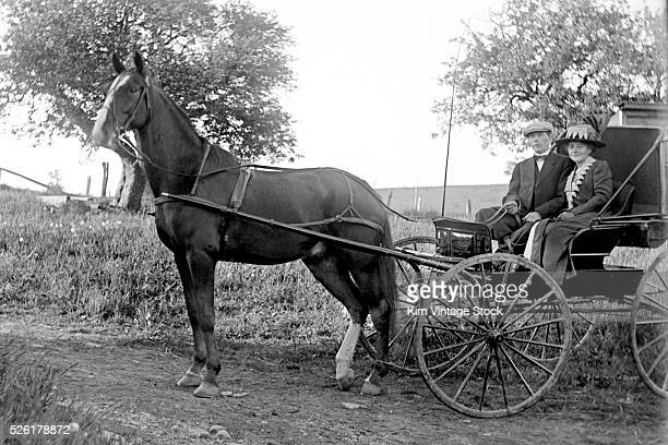 A man and a woman have their portraits taken about ten years apart in the exact same spot in a similar horse and buggy somewhere in New York State