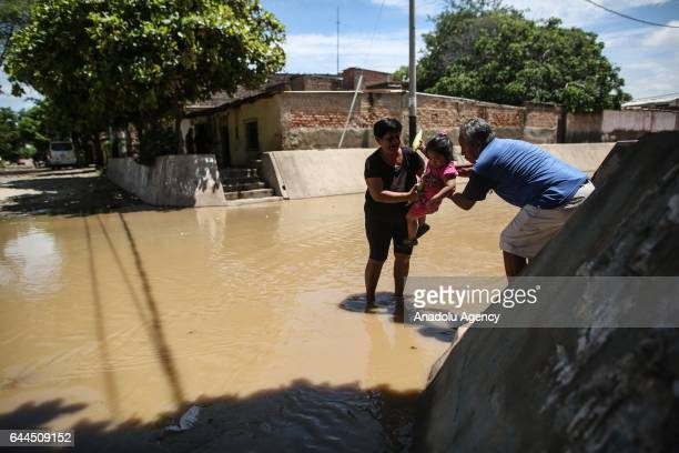 Man and a woman help a girl to pass the floodwaters after a heavy seasonal rainfall caused flood in Sullana, Peru on February 21, 2017. Peru has been...