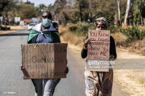A man and a woman hold placards during an anticorruption protest march along Borrowdale road on July 31 2020 in Harare Police in Zimbabwe arrested on...