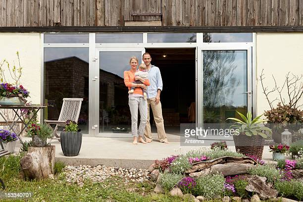 a man and a woman holding a baby standing on the patio in front of their house - voor of achtertuin stockfoto's en -beelden