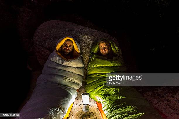 Man and a woman in sleeping bags lit by a lantern at night