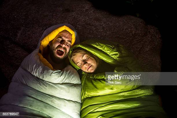 Man and a woman in sleeping bags while Kevin yawns.